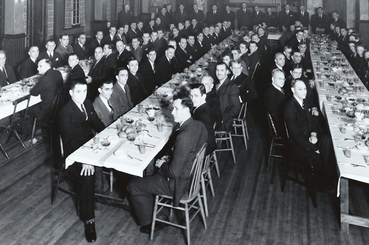 Older image of Union members sitting at table depicting historical Union event