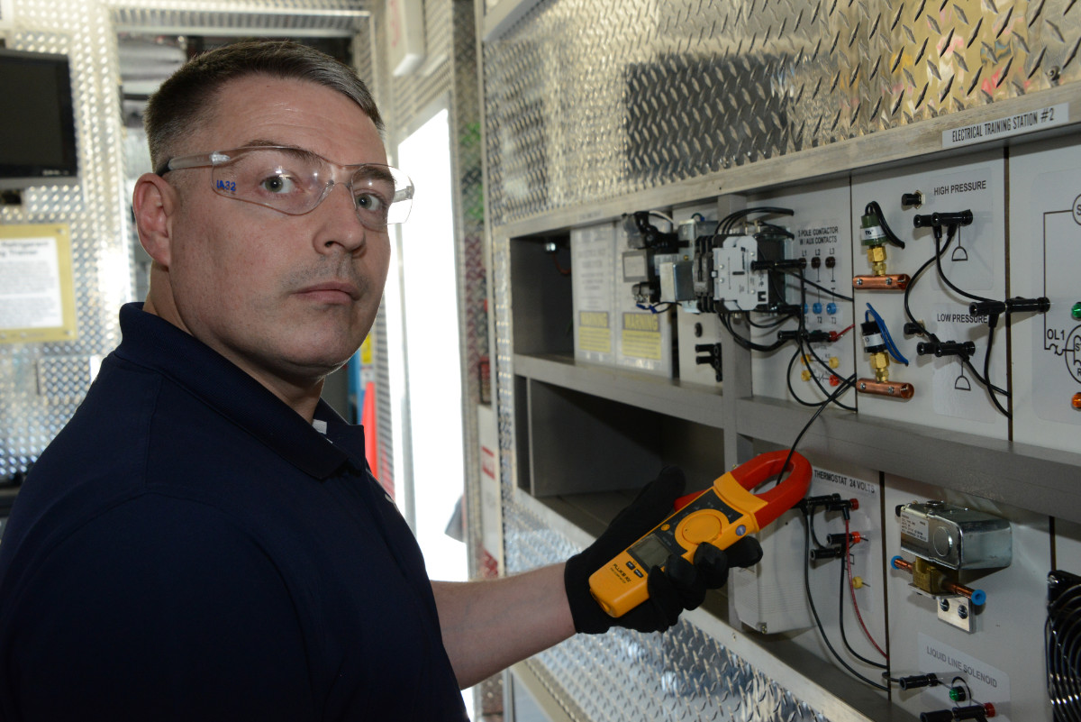 HVAC training instructor holding fluke inductive multi-meter at the electrical training station